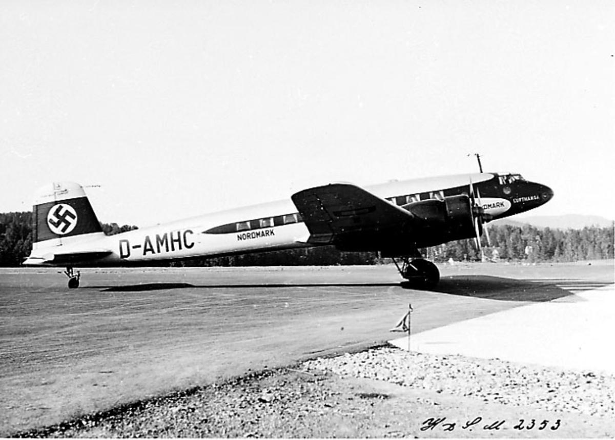 """Lufthavn, 1 fly på bakken Focke-Wulf Fw200 Condor D-AMHC """"Nordmark""""  fra lufthansa. Hakekors på haleparti. Sett fra siden."""