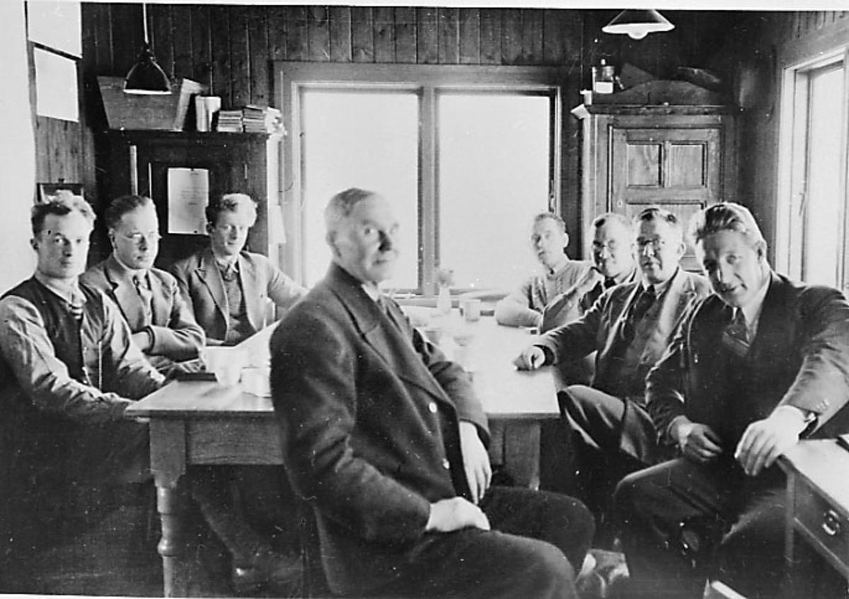 Lufthavn. Inne i anleggsbrakke - kontor, e.l. Flere personer sitter rundt et bord.