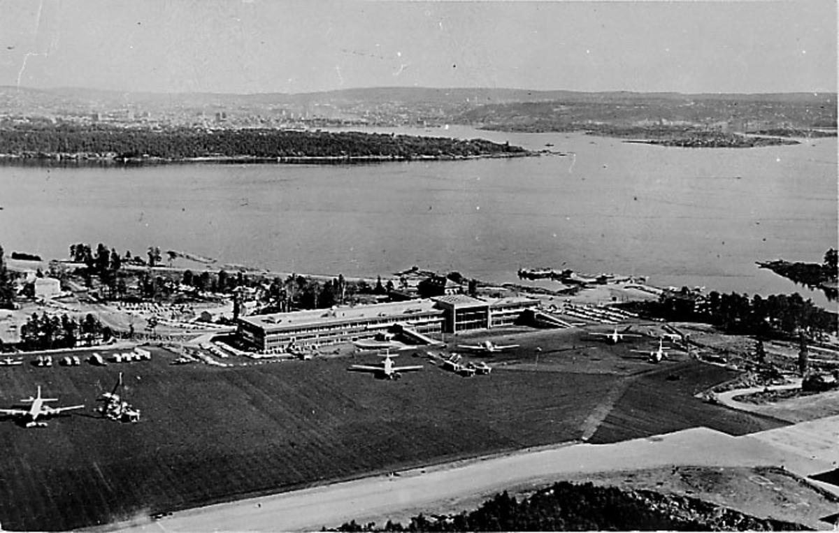 Lufthavn. Oversiktsbilde av flyplassen med parkerte fly og terminalbygning. Fjorden i bakgrunnen.
