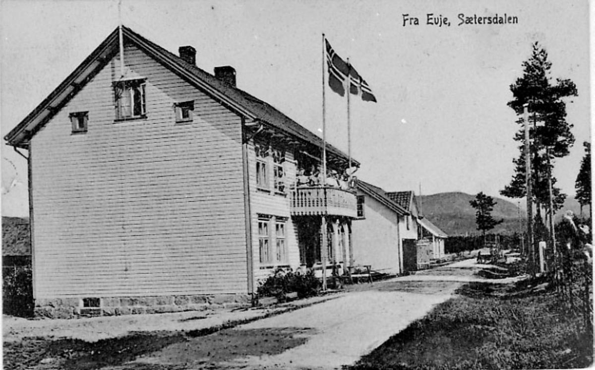 Prospektkort - forsiden. (Fra Evje, Sæterdalen - viser boligbygning med flagg heist ved inngangspartiet).