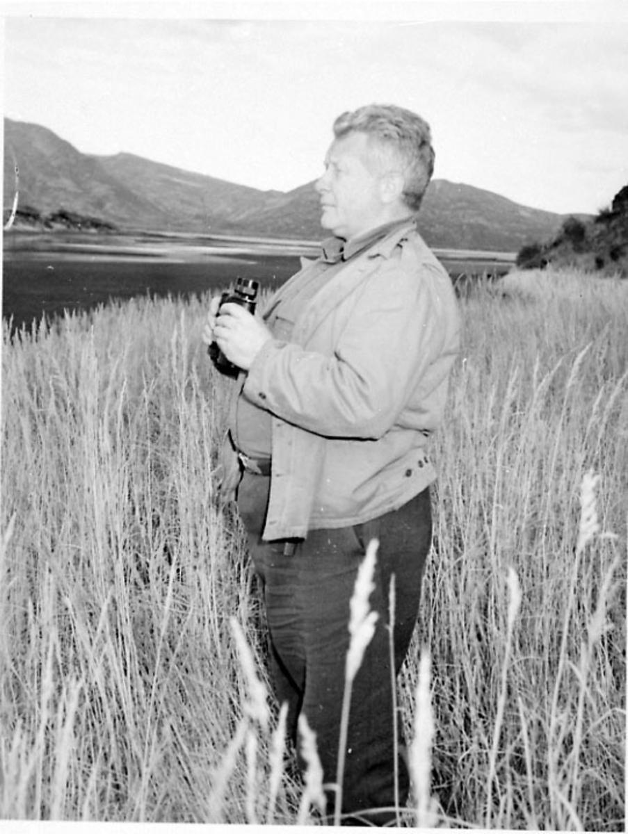 Portrett, 1 person står med en kikkert i hendene i en kornåker- eng. Elv dalføre i bakgrunnen.