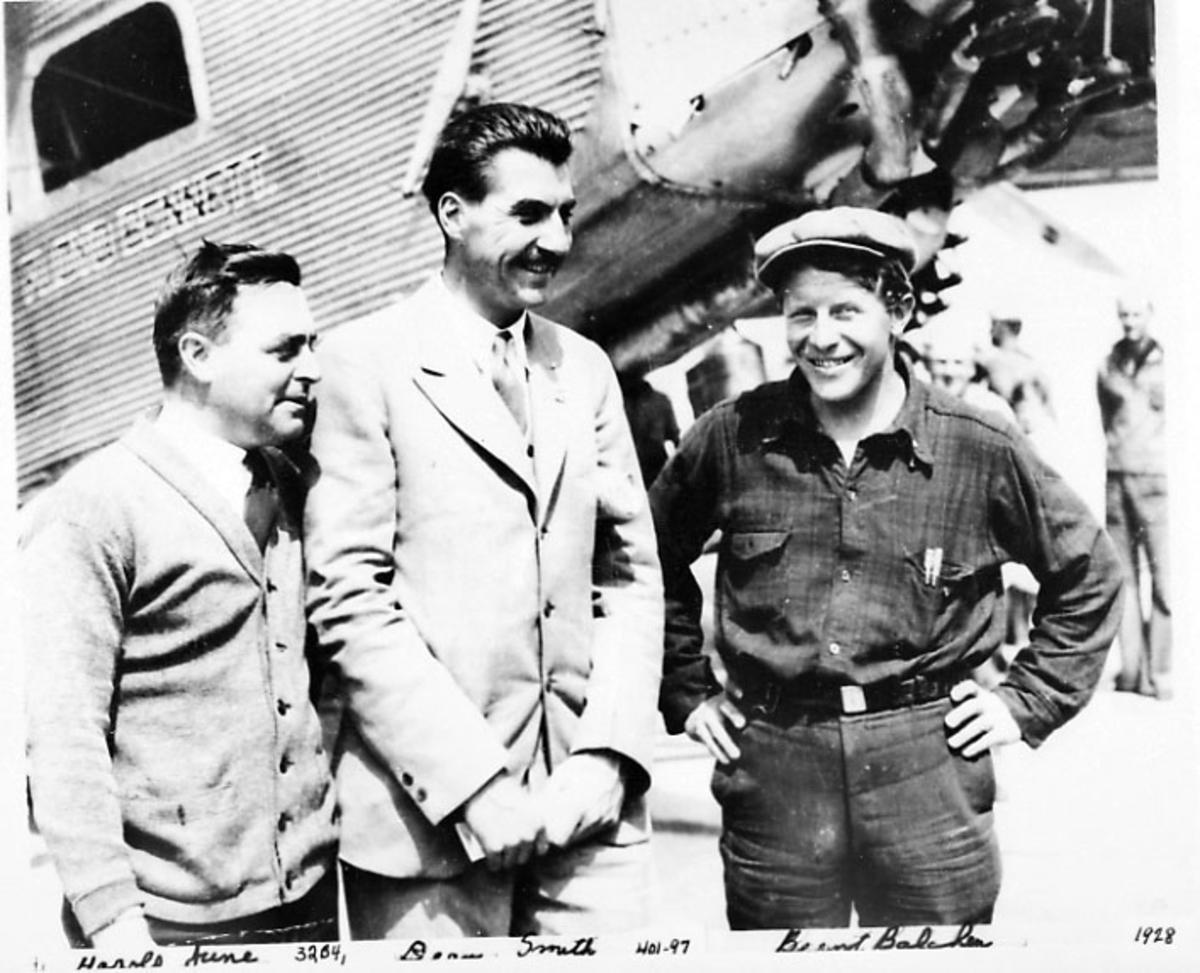 Portrett, 3 personer. Bak sees litt av nesepartiet på et fly.