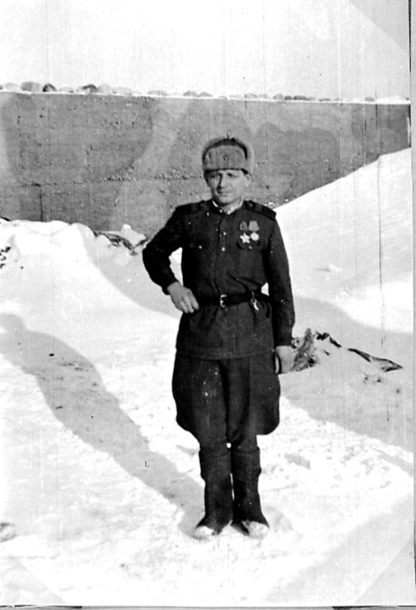 Portrett, 1 person oppstilt, ikledd militæruniform. Tatt utendørs. Snø på bakken.