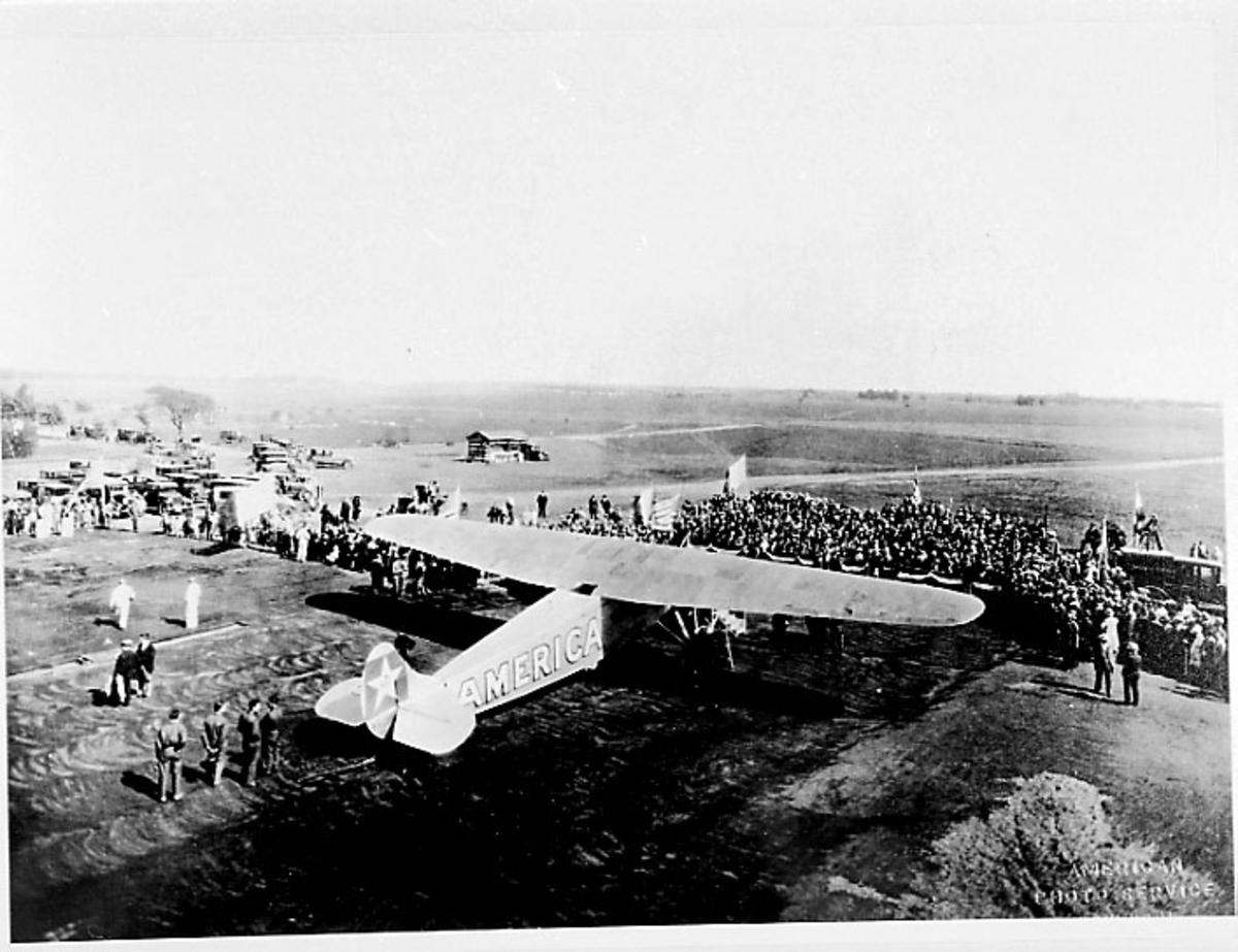 "Lufthavn, 1 fly på bakken, Fokker C-2, C-2A ""America"". Bruker: Admiral Byrd. Mange personer rundt flyet."