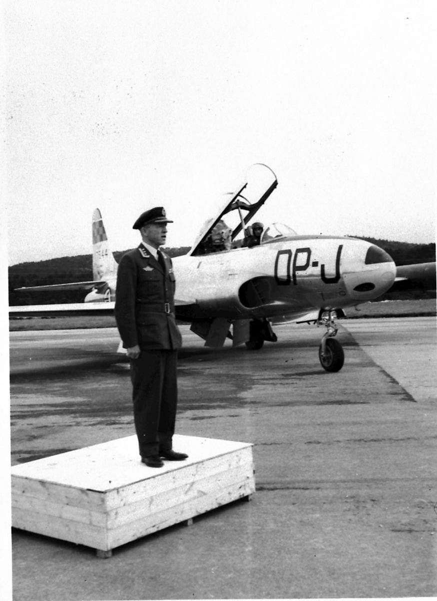 Lufthavn, 1 fly på bakken T-33 T-Beard (treningsfly). 1 person i militæruniform står oppstilt i forgrunnen.