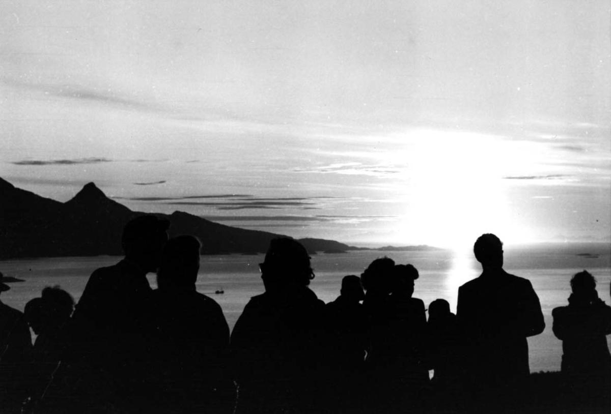 Flere personer i forgrunnen. Ser på solnedgangen i bakgrunnen. (SAS Midnattsolfly)