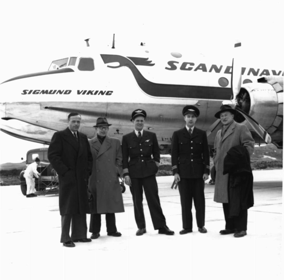 """Lufthavn, 1 fly på bakken DC-4 """"Sigmund Viking"""" fra DNL/SAS. Noen personer oppstilt foran flyet, to av dem flypersonell i uniform."""