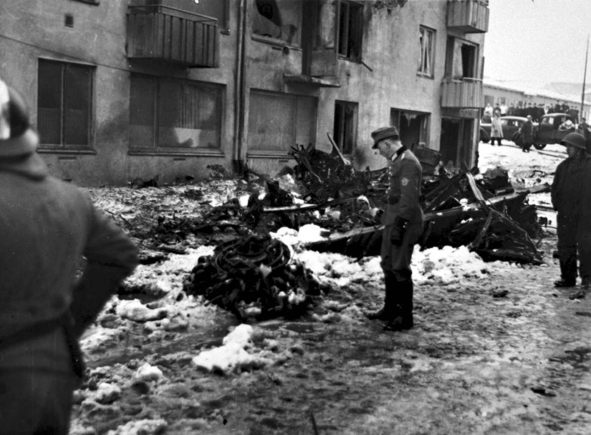 Flyhavari - totalhavari. Flere personer står og studerer restene etter flyvraket.