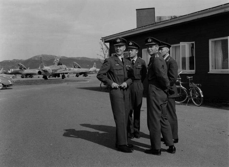 Gruppe  Fire personer i uniform flere fly i bakgr. T-33.