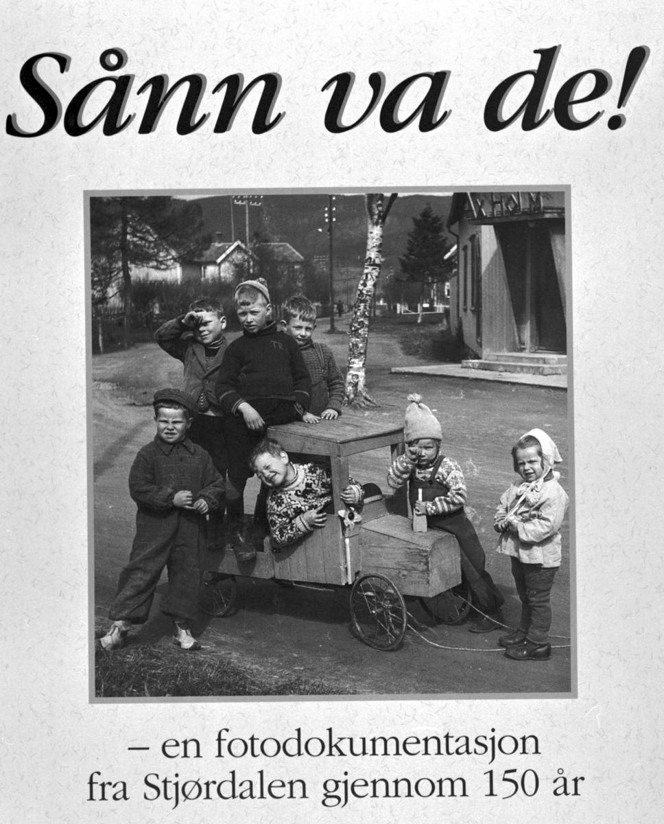 """Foto fra boken """"Sånn var de!"""". Portrett 7 personer, barn i en lekebil."""