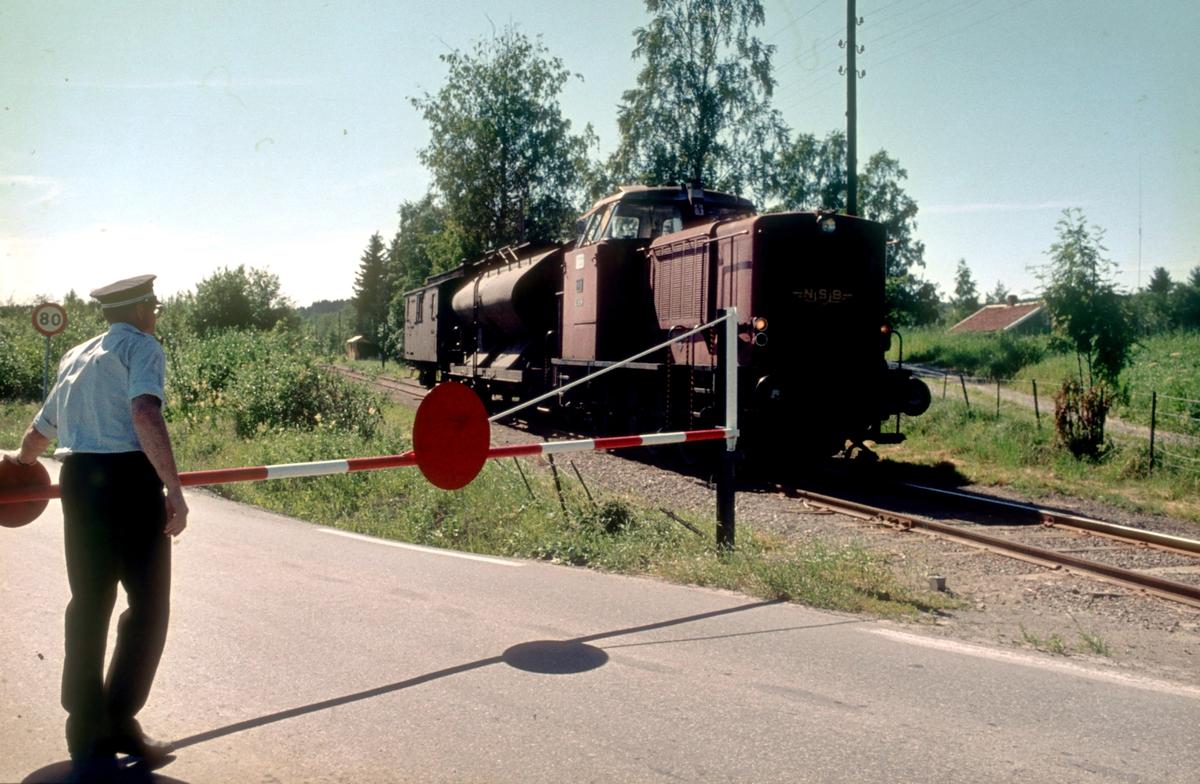 Skreialinjen. Togfører (overkonduktøren) betjener bommen ved en av de mange planovergangene. Bommen stengte for hhv vei eller jernbanen.