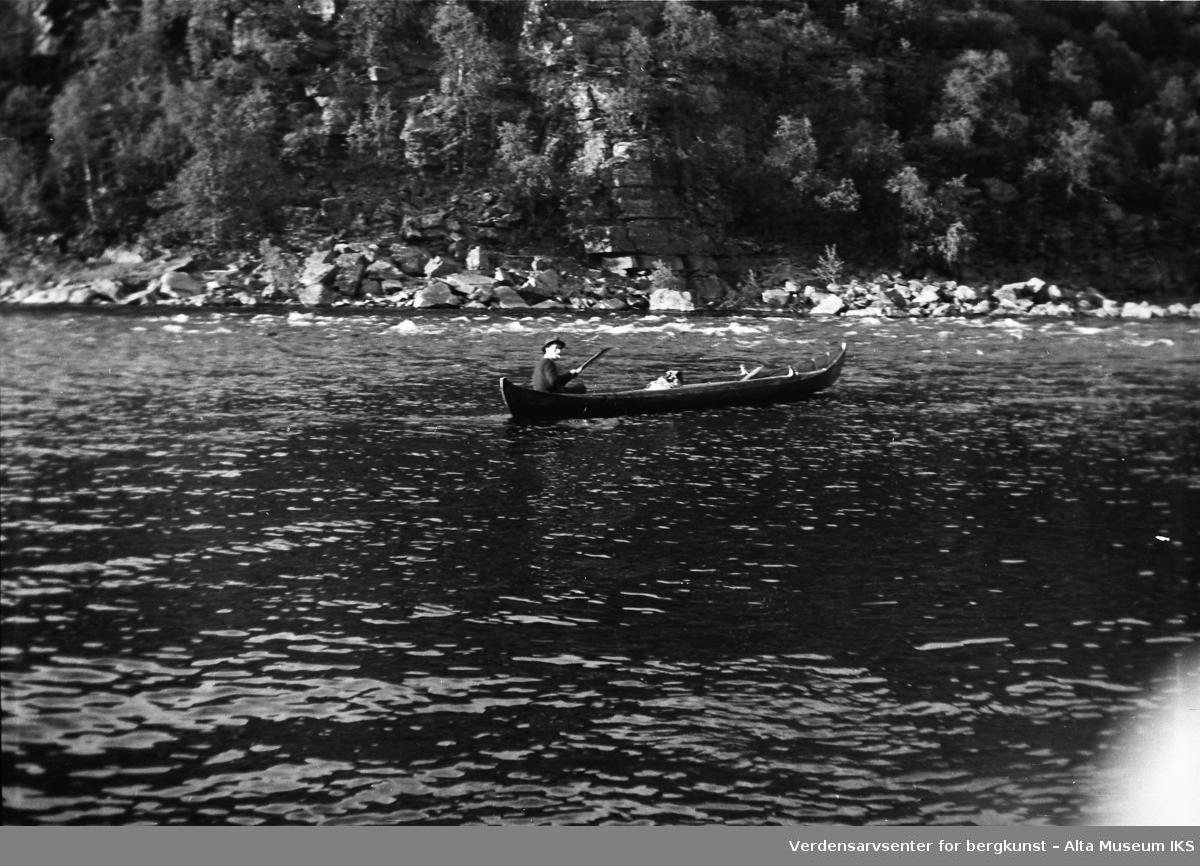 En mann sitter i elvebåten midt på elva.Bildet er tatt i fiskesesongen på sommeren i 1949.