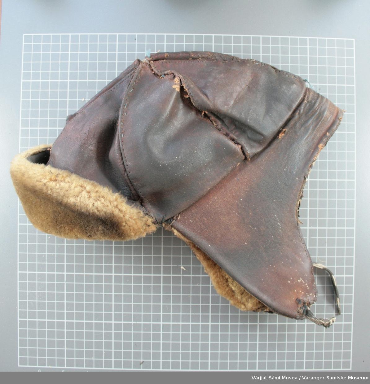 Brun skinnlue med øreklaffer og snor til å knyte under haken. Av brunt skinn, foret med lyst saueskinn.