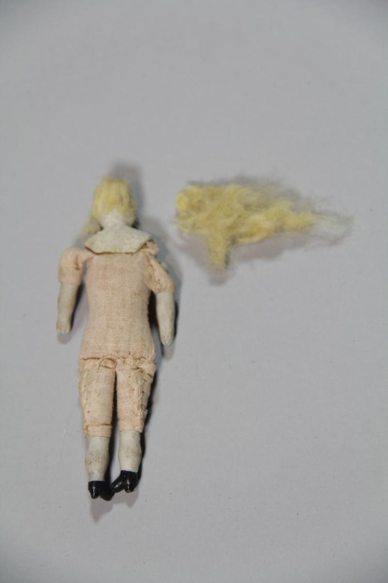 Sydd sammen. Kroppen består av stoff, fylt med mykt materiale. Hals, hode, armer og legger av hardt materiale, trolig porselen. Hår usikkert. Ved siden av gjenstanden ligger mer hår usikkert om det opprinnelig har tilhørt dukken.