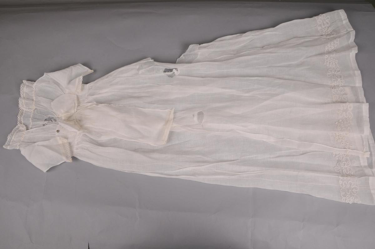 Kvit kjole av tynt, lerretsvove bomullstoff (glassbatist). Kniplingsblonde av bomull framme på arm og rundt kragen. Kjolen har livstykke med isauma arm, krage og ein løpegang med snor for å regulere halsvidda. Livstykket og skjørtet er rynka til kvar side av eit magabelte som er dekorert med banddekor. Kjolen er open midt bak og har to knappar til lukking, som er under ei fastsauma sløyfe. Nedre del av kjolen har lik banddekor som magabeltet. Handsaum og maskinsaum.