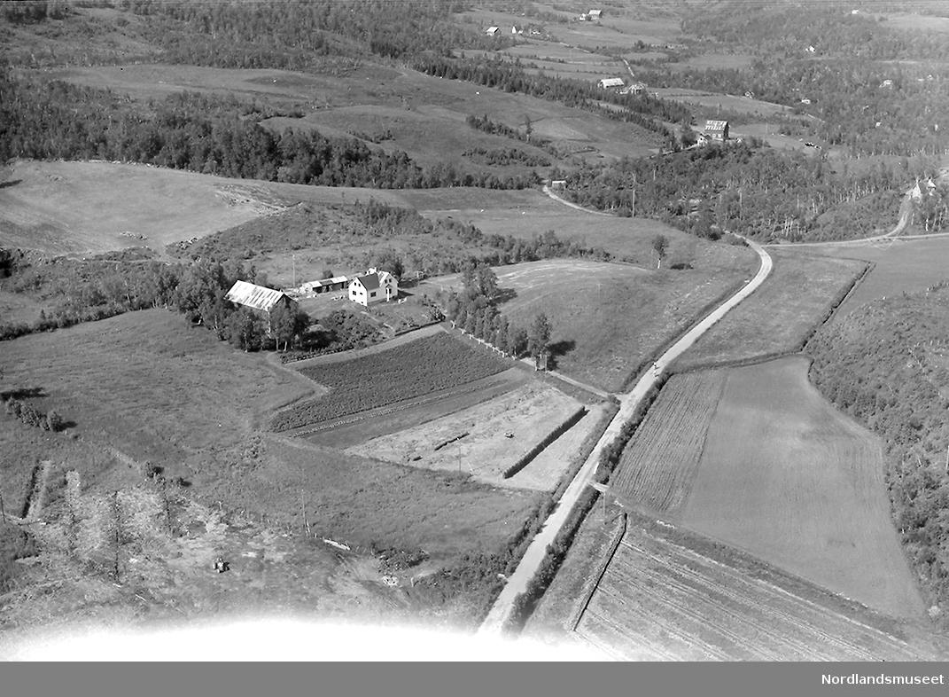 Flyfoto. Eiendommen til Odd Sandberg? Dyrka mark, bygninger. Veier og en del trær. Flere eiendommer bak.