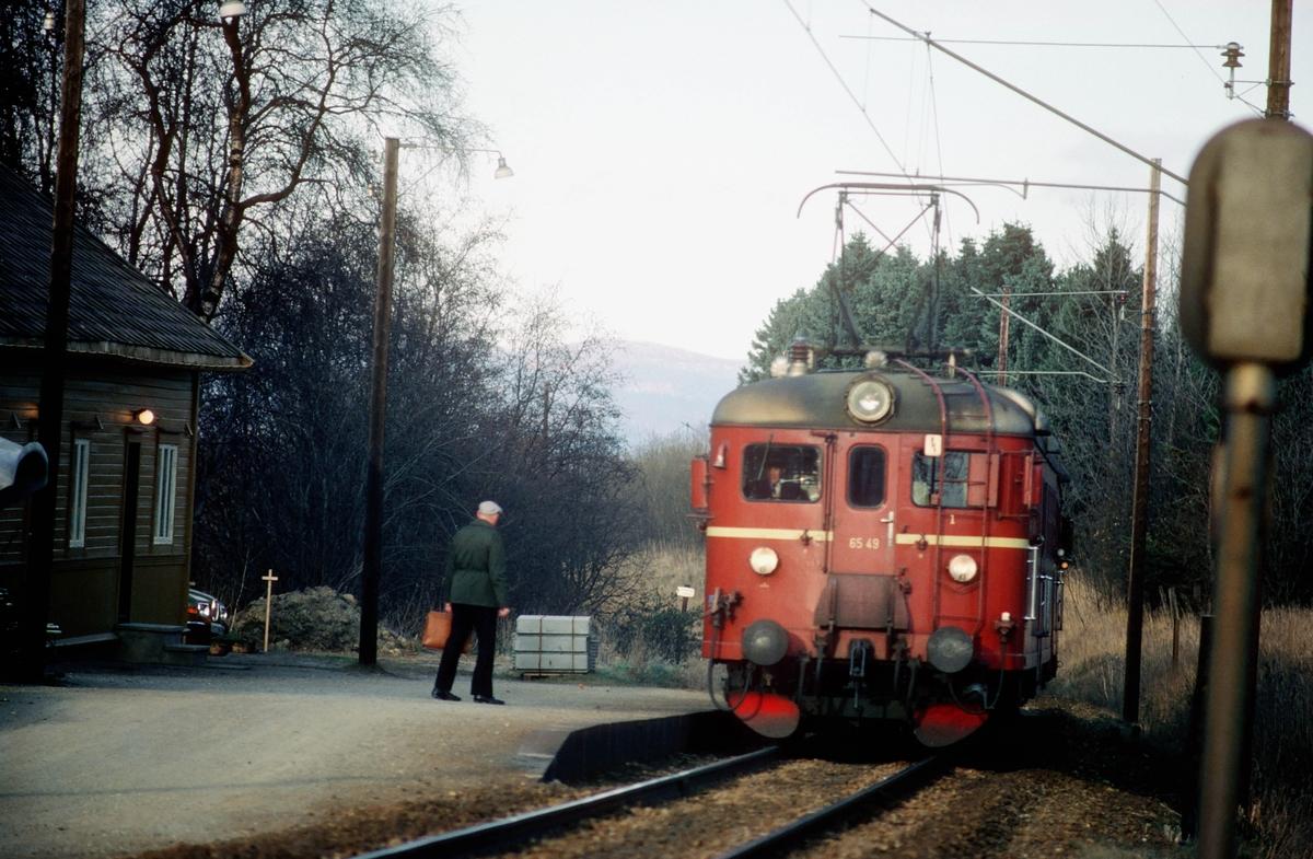 En reisende venter på lokaltoget til Støren på Stavne holdeplass. NSB elektrisk motorvogn BM 65c 49.