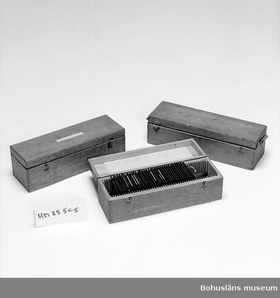 Två lådor av betsad furu, zinkade hörn. Båda innehåller skioptikonbilder 8,2 x 8,2 cm., samtliga föreställande köksväxter. Ena lådan  innehåller 36 bilder och den andra 27 bilder.  Jfr med UM025506 och UM025507.