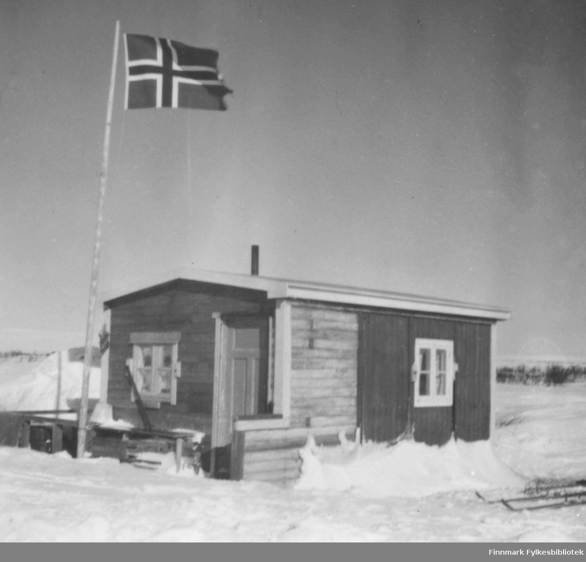 Hytte ved Sjåbuselva i Vadsø. Den tilhørte Edith og Arne Berg, Ragnhilds tante og onkel. Flagget er heist, ski i snøen ved hytta