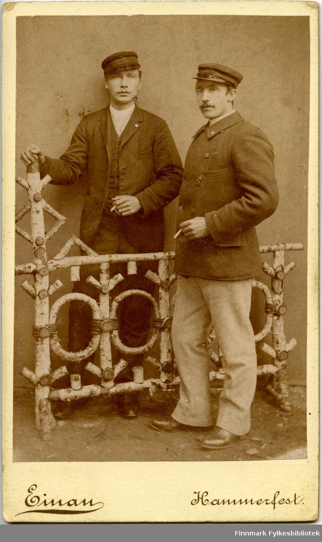 Visitkort. Portrett fra maskinist Olsen og telegrafist Holst. Mennene står ved en gjerde lagt av bjørkekvister i studio til fotografen. Mennene er kledd i korte jakker og luer og har sigaretter på hand.
