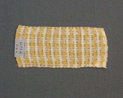 Prov till gardin vävd i tuskaft med hål, provet har bomullsgarn i varp och inslag.Ytterligare prov och vissa vävuppgifter finns i pärm gardiner A, litt B 216 a.