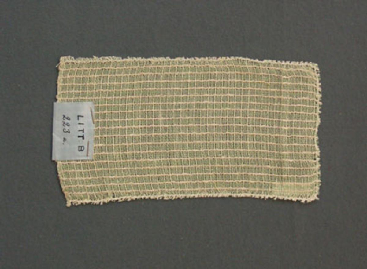 Prov till gardin vävd i tuskaft och stramaljbindning, provet har bomullsgarn i varp och bomullsgarn och frottégarn i inslag.Ytterligare prov och vissa vävuppgifter finns i pärm gardiner A, litt B 223 a.