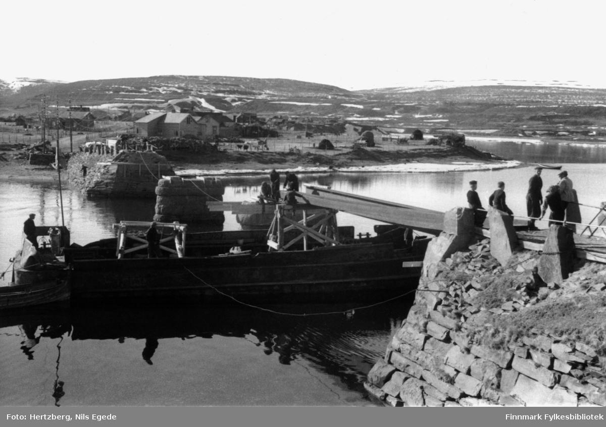 Bygging av Vestre Jakobselv bru. En båt ligger under den nylig påbegynte bruen. To menn er ombord i båten, fem menn jobber på bruen. Tre gutter står å ser på arbeidet. I bakgrunnen ser man noen hus.
