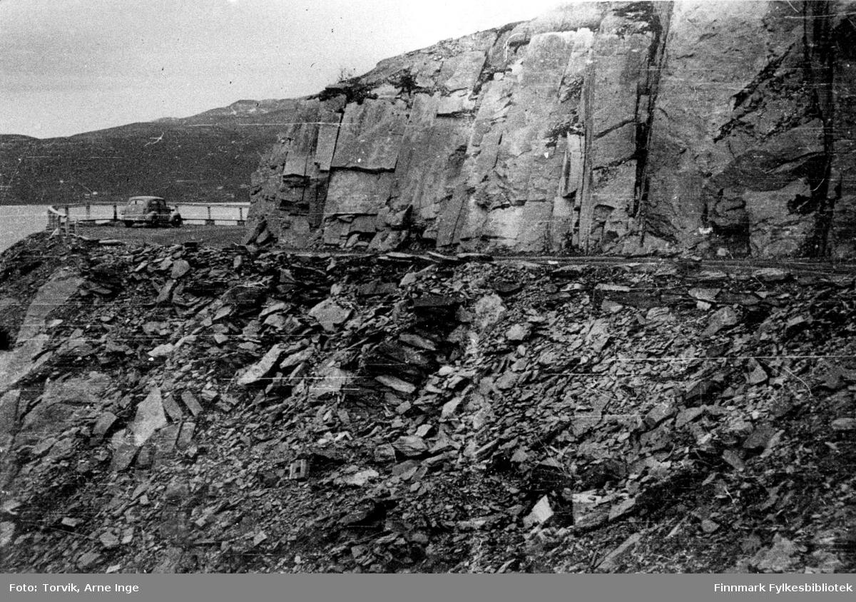 Fjellskjæring i oppstigningen fra Sjursjok. Her hadde tyskerne sprengt ved tilbaketreknigen høsten 1944. En udetonert bombe fly bombe lå igjen i en velbevart stikkrenne. Bomben ble fjernet av militæret i juni, dagen før utbedringsarbeidet av dette veipartiet ble påbegynt.