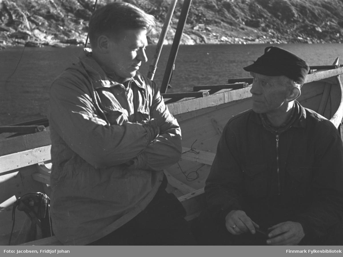 To menn sitter ved siden av en robåt. I lys jakke til venstre sitter Erling Jensen som var kinobestyrer. Ved siden av han, i mørk jakke og skyggelue, sitter Fritz Hay som var banksjef i Finnmark privatbank. Et fjell med bratte sider ses i bakgrunnen.