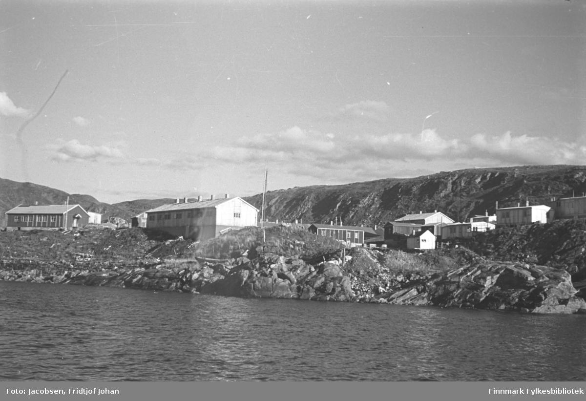 Området Batteriet i Hammerfest fotografert fra sjøen. Flere brakker står på området og opp mot bydelen Haugen. Helt til venstre ligger Postverkets funksjonærbolig. Fjellet i bakgrunnen er Salen.