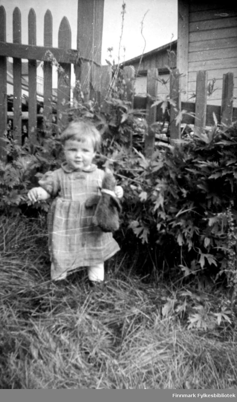 Brit Stok, populært kalt Bitten, i hagen en sommerdag. Solen skinner og hun er iført en heldekkende, rutet kjole og bærer et kosedyr i handa