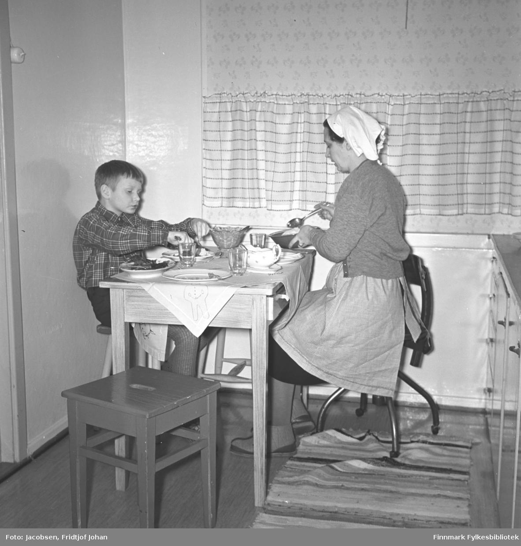 Aase og sønnen Arne Jacobsen ved middagsbordet på kjøkkenet i Storvannsveien. Arne har en rutet skjorte og ganske lys bukse på seg. Aase har et mørk skjørt, med et lyst forkle over og en litt mørkere jakke. På hodet har hun et hvitt skaut/tørkle. Arne sitter på en trekrakk og Aase på en kontorstol. Tallerkener, glass, skål og bestikk ligger på bordet mellom dem. En krakk og en rye ses på gulvet og en liten del av kjøkkeninnredningen ses helt til høyre på bildet. En lys gardin henger foran vinduet.