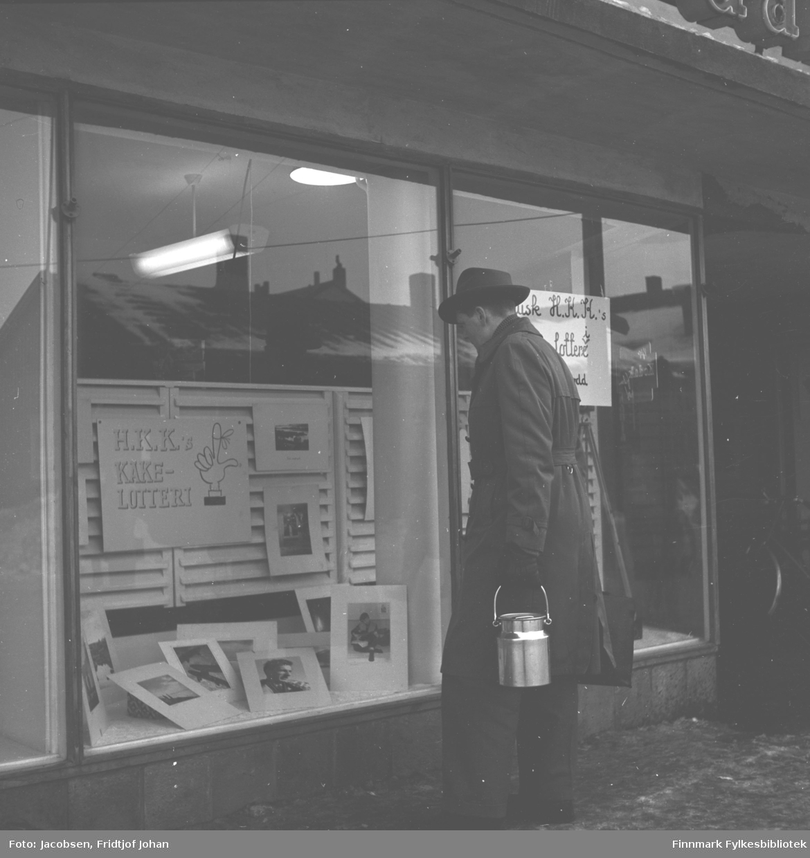 Tor Todal kikker i et utstillingsvindu til en butikk i Hammerfest. Han har mørke klær på seg, frakk/bukse og hatt. Han har en blankt spann i sin venstre hånd. Nederst i vinduet ligger flere fotografier og på veggen henger en reklameplakat for H.K.Ks kakelotteri.