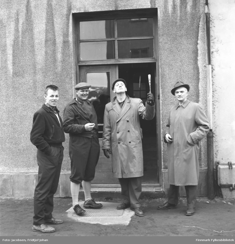Gruppeportrett av fire unge menn ved et inngangsparti i Sjøgata, gamle Sparekassens inngang. De er fra venstre: Gunnar Nilsen kleddt i mørk bukse og mørk jakke. Ved siden av står Tor Todal iført mørk jakke, mørke knebukser og lyse strømper. Han har en sixpence på hodet og en sigarett i hendene. Torbjørn Johansen holder et skrujern i de hanskekledte hendene og er iført lys frakk og mørke bukser med en skyggelue på hodet. Lengst til høyre står Fridtjof Jacobsen. Han har en lys frakk, mørk bukse og hatt på hodet. Inngangdøren er mørk og to-delt med et sprossevindu over. Et takrennenedløp henger på den lyse murveggen.
