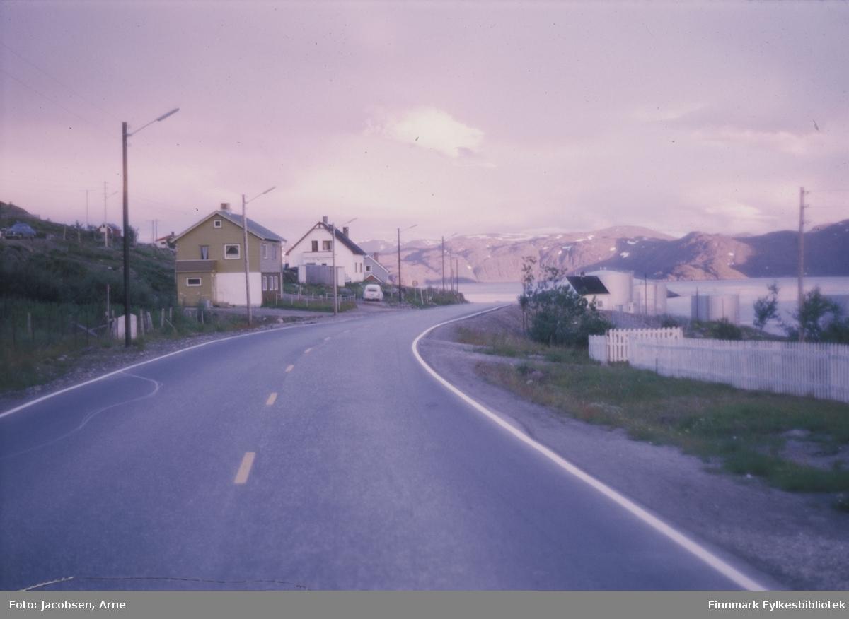 Fjordaveien, riksvei 94, gjennom Rypefjord en fin  sommerdag. Lite bebyggelse i forhold til dagens dato, men 3 hus ses langs veien og et par kan skimtes helt til venstre. Til høyre for veien står ett hus og nedenfor det se vi tankanlegget på Storneset. Lysstolper står langs veien og et par biler står parkert ved husene. Helt til venstre står en bil parkert i Bjørkåsen. Man ser ingen hus der, men byggingen på boligfeltet er nok kommet i gang. Til høyre står et hvitt stakittgjerde. Sjøen oppe i bildet er Strømmen og i bakgrunnen ses øya Seiland.