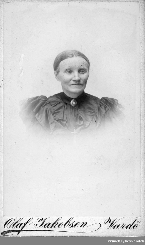 Portrett av Anna Christine Jacobsen, født Vibe. Hun var gift med smedmester Ole Sigfrid Jacobsen, Vardø. Portrettet viser henne pent kledt i en mørk silkekjole eller bluse. I halsen har hun en brosje. Fotografen er hennes sønn Olaf Jacobsen