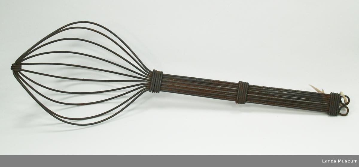 """Visp av ståltråd. Bygt opp av 5 lengder tråd kor den ein er brukt som festpunkt nederst på vispen. 3 festepunkt på skaftet, og øverst er det 2 """"auge"""" til oppheng."""