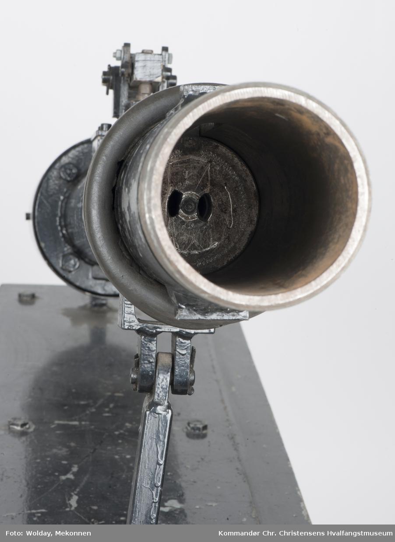 """""""Drivkraften består av to spiralfjærer, den ene inni den andre. For  å stramme fjærene ble det laget en muffe, som ble skrudd fast på tuppen av kanonløpet. Og gjennom denne ble det anbrakt en gjenget stang med sveiv i enden, slik at fjæren kunne sveives i spenn. Utløsermekanismen kan sees på oversiden av kanonløpet på bildet til venstre. Det består av en hake på en vippearm. Da det trengtes stor kraft for å utløse vippearmen ble det her benyttet en ganske  kraftig hammer. I forkant ble kanonløpet festet med en strekkfisk, slik at høyden på kanonløpet kunne reguleres, så det passet til det til enhver tid passende treffpunkt. Med denne kanonen kunne champagneflasken skytes en 20 til 30 meter, og flasken kom ut med stor fart""""."""