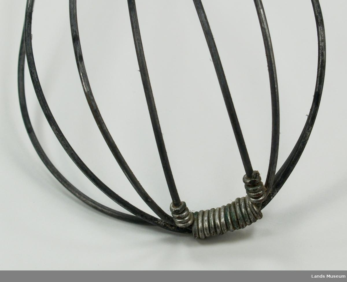 Strengarbeid. Visp med treskaft og ståltråd. 4 tråder. Eit festepunkt i bøyen framme og festa til treskaftet med ein anna ståltråd. Hempe til oppheng i enden på treskaftet.