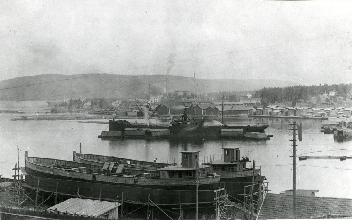 """Lastande fartyg i Kramfors, 1920-tal? Bakon den av takpråmar omringade virkeslastade ångaren ses östra sågens tre hyvelmagasin. I förgrunden två av de tre ryska pråmar som Kramfors Bolag använde för att hämta kalksten från Gotland eller Kisaka från Rönnskär. Pråmarna kallades i folkmun för """"bolsjevikerna"""" och ligger här upptagna för översyn."""