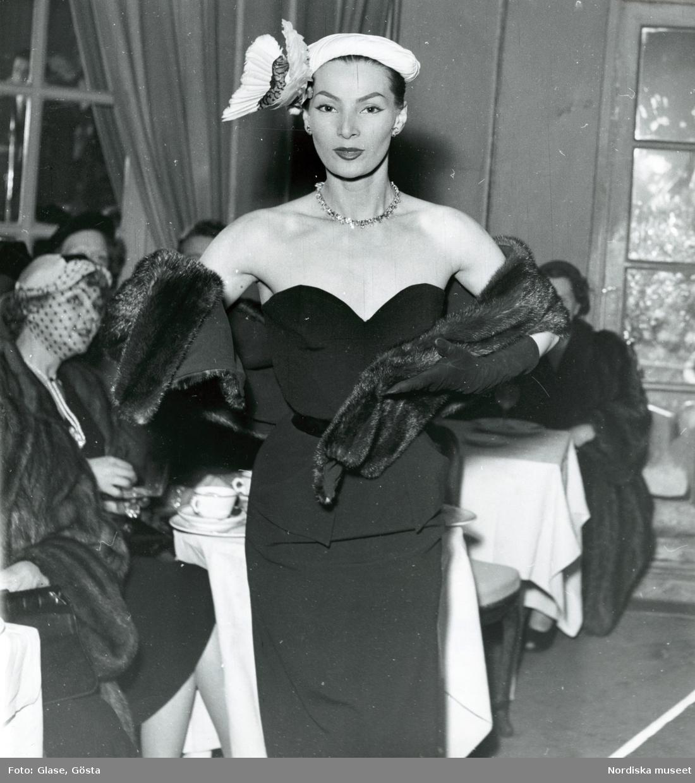 Modevisning - Modell i svart aftonklänning, pälsboa och vit hatt med fjäderdekoration.