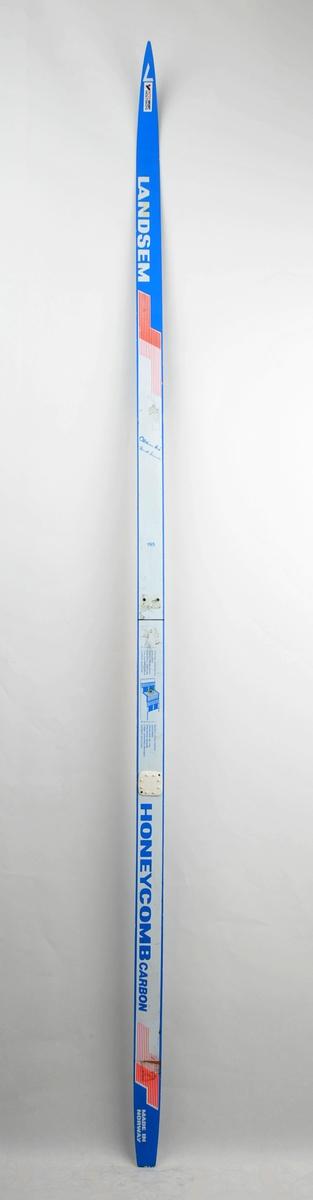 Langrennski laga av glasfiber, karbonfiber og med aluminium i kjerna. Kvit overflate, raud og blå dekor/skrift, såle av plast. Dekorera med signaturane til Oddvar Brå og Berit Aunli. Det har vore bora hol til bindingar, ein hælknott sit på.