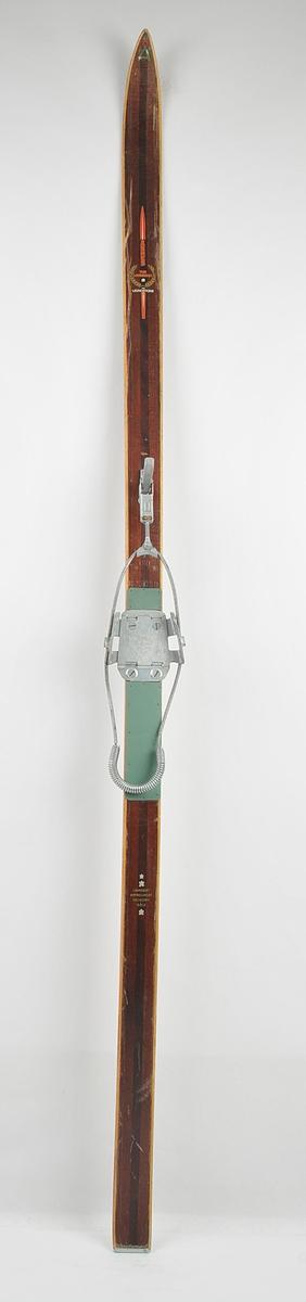 Langrennski laga av tre. Måla mørk brune på overflata, med lysare kantar. Lignostone i skiet. Lys såle med mørke kantar. Metallforsterking bak.  Skibindingen er ein kabelbinding av merket Gresshoppa. Grøn gummimatte under foten, metallplate med vaier og eit regulerbart jernspenne framme til å stramme vaieren med.