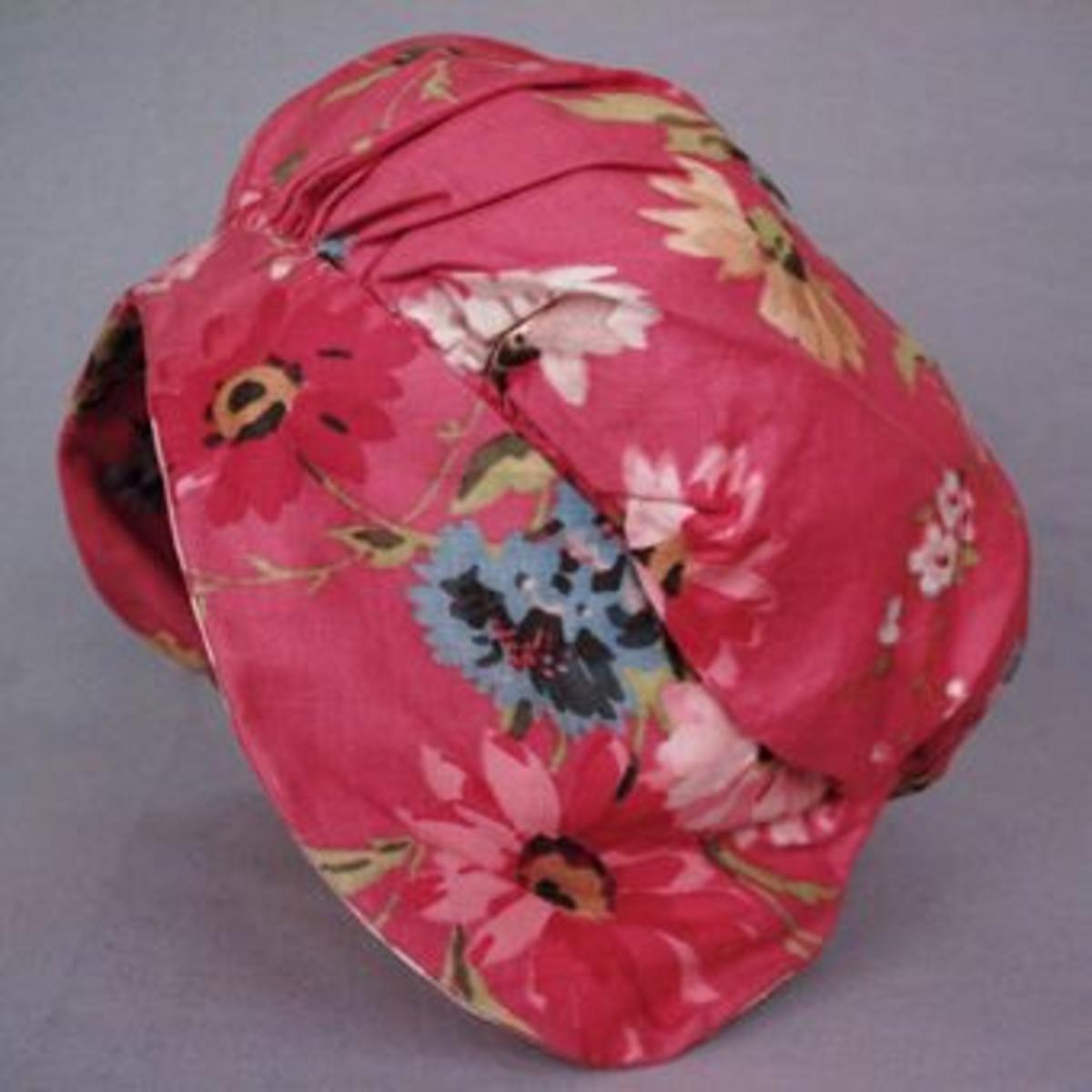 Mjuk mössa i bomullstyg till Sunnerbodräkten. Tyget är vävt i satinbindning och har rosa, röda, gula, vita och blå blommor på rosa botten.