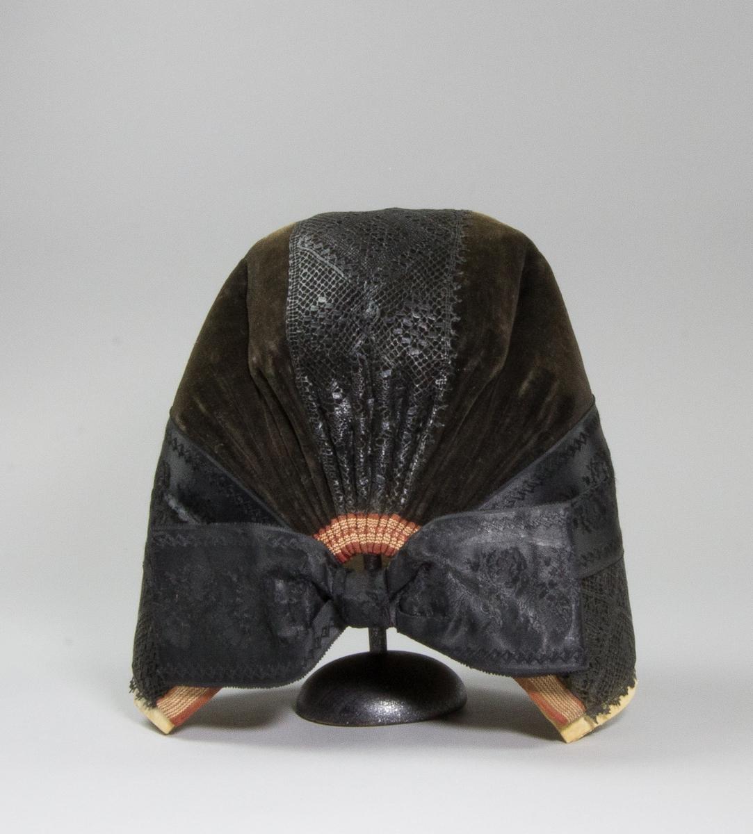 """Bindmössa, """"svarstluvva"""", till högtidsdräkt för gift kvinna från Delsbo socken, Hälsingland. Tillverkad av svart fabriksvävd sammet monterat på en stomme av grovt handvävt och klistrat linnetyg, tuskaft. Längs framkanten samt från pannan bakåt över hjässan till nacken sitter en handknypplad uddspets, 90 mm bred, svartfärgad. Ovanför spetsen sitter ett svart jacquardmönstrat sidenband, 68 mm brett, runt kullen. Denna mössa har också en """"gvitrimpa"""" under framkanten: en fastlimmad remsa dubbelvikt bomullstyg med en smal uddspets, 5 mm, synlig längst ut. Samma siden band till rosett i nacken. Sammetens stadkant, vävd randig av silke i rött och gult, har utnyttjats till dekorativ nederkant på mössan. Tio veck på var sida i nacken."""
