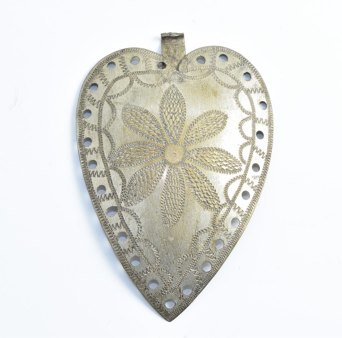 Tynn, hjerteformet spenne i sølv dekorert med en siselert blomst med åtte kronblader. Spennen er gjennomhullet på kanten.