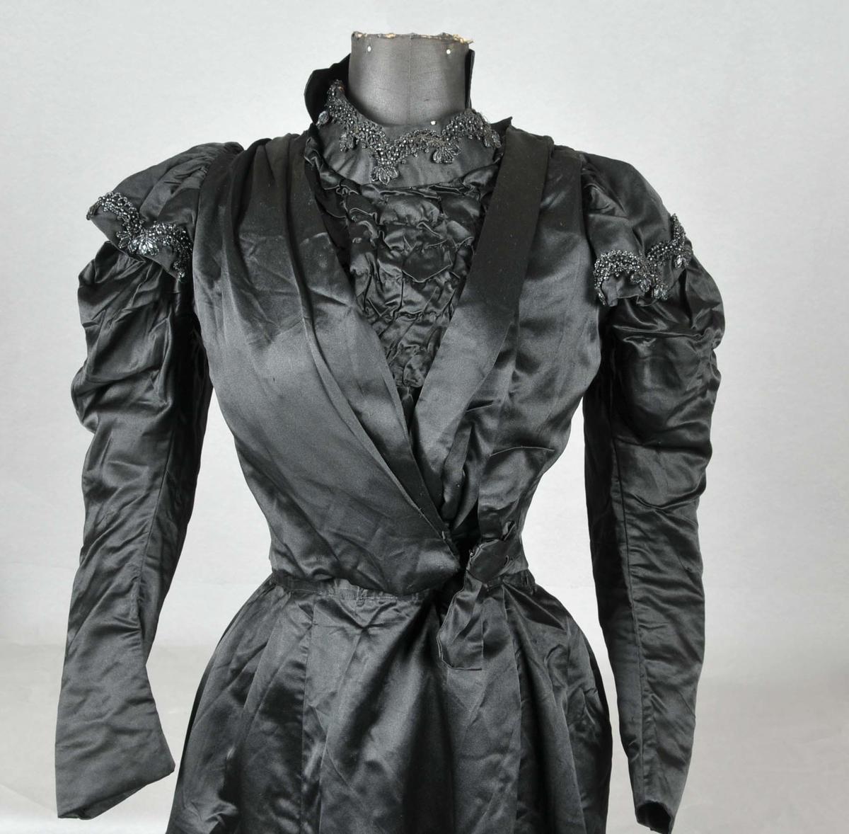 Kjolen er todelt. Svart med perlebroderi.