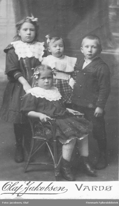 Barn tre jenter en gutt. Jentene har broderte krager og kjoler, sløyfer i håret, gutten har dress. Studio ateliere Albumet med bildet kommer fra Ekkerøy, kanskje de bodde der.