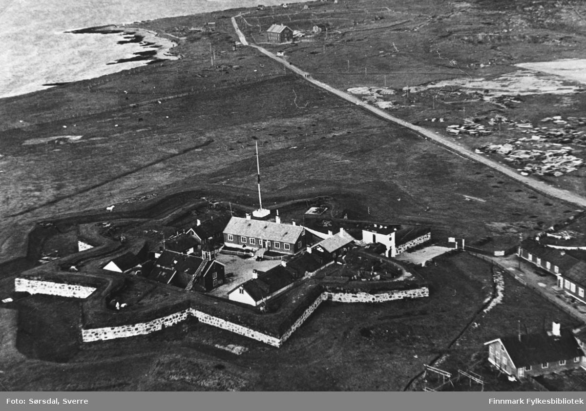 Flyfoto av Vardøhus festning. Vi ser festningvollen formet i stjerneformasjonen og bygningene i midten. Ser også byen i bakgrunnen.