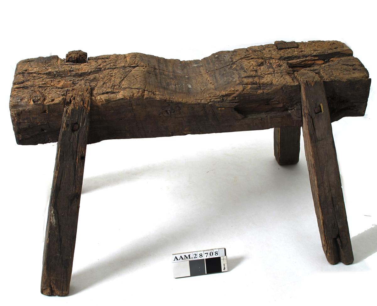 Bukk med fire skråstilte bein. Laget av en firkantet bjelker innfelte bein, som er spikret fast. Spikerhodene forteller at gjenst er fra 1800-tallet.  Spor som tyder på at bukken er brukt til som understøttelse av rundholt  (master og bommer til seilskuter) i et verksted, et rundholtverksted.